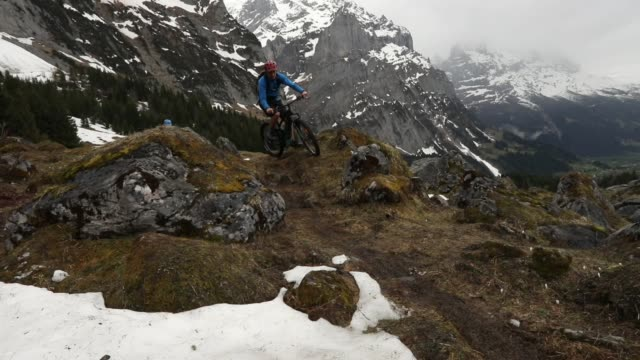 junge männer fahren e-mountainbikes über schwierige gebirgsgelände - unterwegs stock-videos und b-roll-filmmaterial