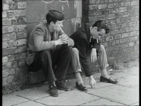 vidéos et rushes de young men sit on a step smoking - 1950 1959