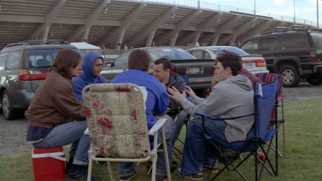 Young men sitting on folding chairs around grill and talking at tailgate party