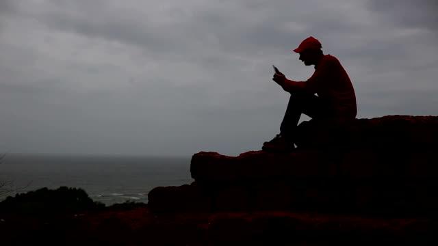 vidéos et rushes de jeunes hommes assis sur le vieux mur et à l'aide de smartphone - silhouette contre jour