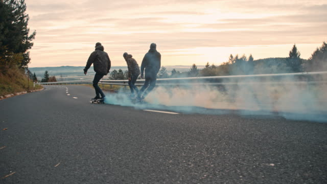 ms young men skateboarding with smoke bombs on road - skateboarding stock videos & royalty-free footage