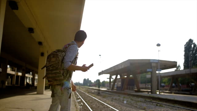 young men solo traveler on the railroad station waiting for a train - stazione video stock e b–roll