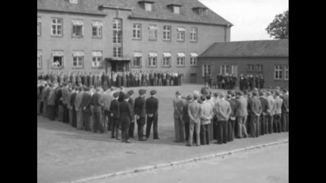 vs young men stand in rows around square bordered by buildings / uniformed officers stand around table as one reads out loud // large ship cruises... - 1951 stock-videos und b-roll-filmmaterial