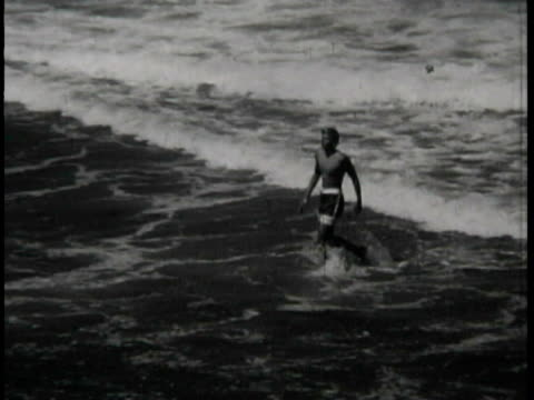 Young men surfing crashing falling off surfboards / sitting and standing on the beach watching Surfing at California beaches on January 01 1964 in...