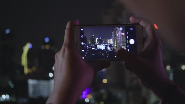 cu young men taking and sending a photo of cityscape at bangkok - photographing stock videos & royalty-free footage