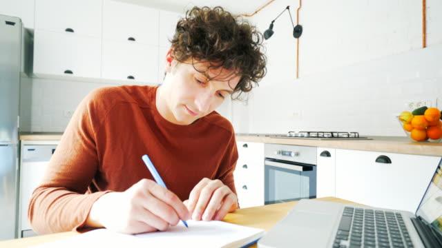 vidéos et rushes de jeunes hommes à prendre des notes lorsque vous utilisez un ordinateur portable. - recherche