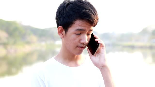 stockvideo's en b-roll-footage met jonge mannen praten op mobiele telefoon - alleen één tienerjongen