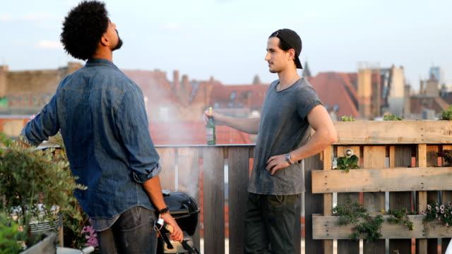 stockvideo's en b-roll-footage met jonge mannen praten terwijl je door barbecue grill - barbecue sociale bijeenkomst