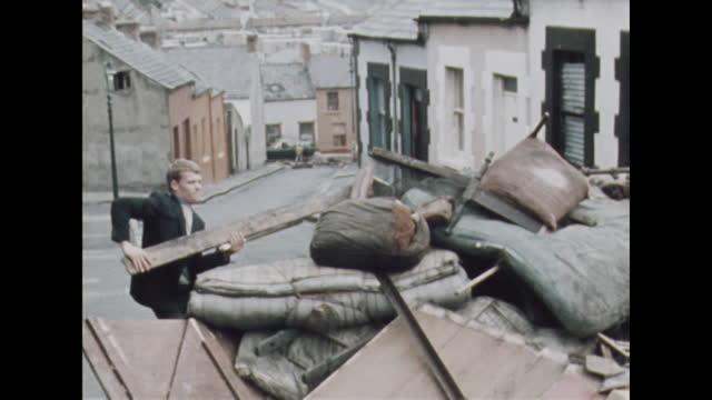 young men tend to a street barricade in the bogside district of londonderry, northern ireland, prior to the apprentice boys parade; 1969. - boundary stock videos & royalty-free footage