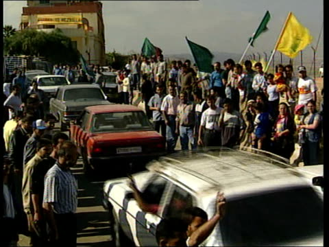 young men throwing stones at barbed wire fence hizbollah supporters with flags tilt down to cars away along street barbed wire fence tlms young men... - hezbollah stock videos & royalty-free footage