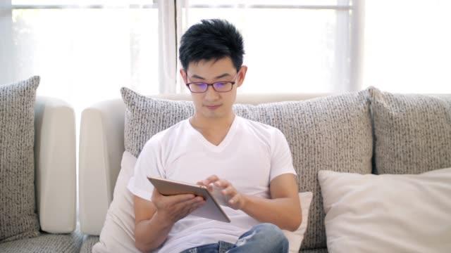 若い男性を使用して、タブレットのソファの上に触れてリラックス時間自宅でスローモーション - タブレット使用点の映像素材/bロール