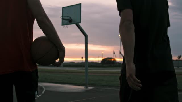 cu junge männer gehen von outdoor-basketballplatz in der dämmerung. zwei freunde gehen aus outdoor-basketball - basketball stock-videos und b-roll-filmmaterial