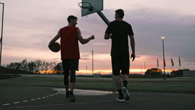 vidéos et rushes de ms jeunes hommes marchant hors du terrain extérieur de basket-ball au crépuscule. deux amis marchant outre du basket-ball extérieur. - basket ball