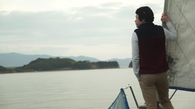 Giovane uomo, guardando il mare con Yacht