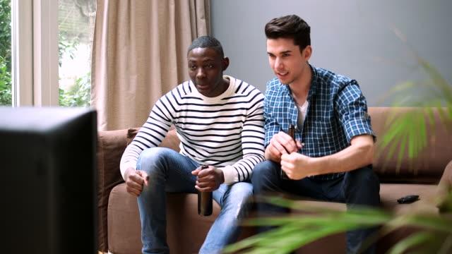 vidéos et rushes de ms young men watching tv and giving high-five - seulement des jeunes hommes