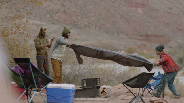 young men work together to set up a tent at a utah camp site. - cooler container stock videos and b-roll footage