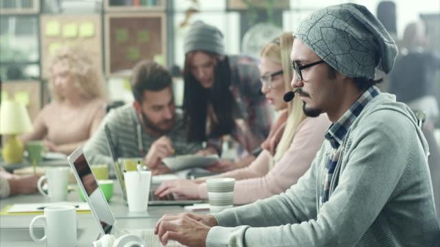 vidéos et rushes de jeunes hommes travaillant dans le centre d'appels - e commerce