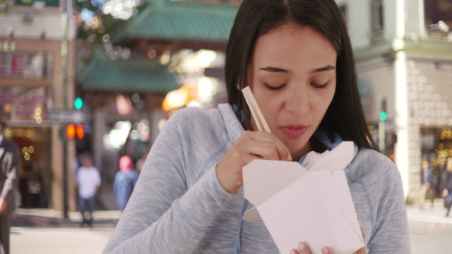 young mexican woman eating chinese food - noodles stock videos & royalty-free footage