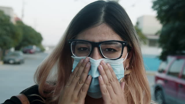 young mexican woman in her twenties putting on her n95 covid face mask used to flatten the curve and slow the spread of the covid-19 corona virus during the pandemic in juárez, chihuahua, in northern mexico near the us/mexican border - northern mexico stock videos & royalty-free footage
