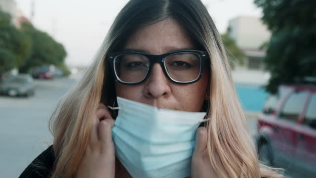 young mexican woman removing her n95 covid-19 mask used to flatten the curve and slow the spread of the corona virus in the northern city of juárez, chihuahua mexico during the pandemic - northern mexico stock videos & royalty-free footage