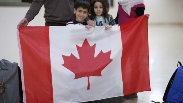 young middle eastern family immigrating to canada waving a flag - bandiera del canada video stock e b–roll