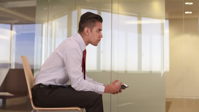 young millennial hispanic business professional sitting in office chair talking to colleague off camera - neckwear stock videos and b-roll footage