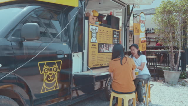 young millennial people buying food and drink from food truck - foodie stock videos & royalty-free footage