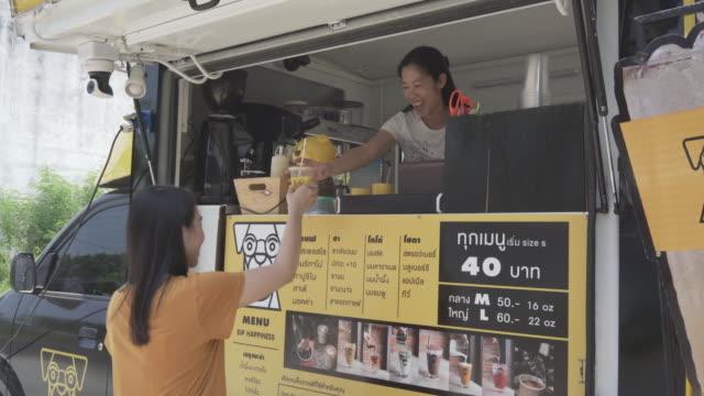junge millennial-leute kaufen essen und trinken bei food truck - kiosk stock-videos und b-roll-filmmaterial