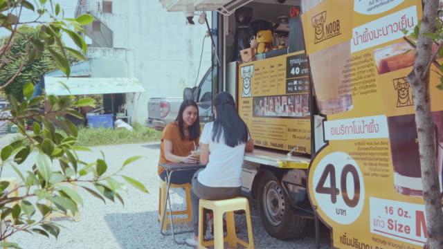 junge millennials kaufen lebensmittel und getränke von food truck - gastwirt stock-videos und b-roll-filmmaterial
