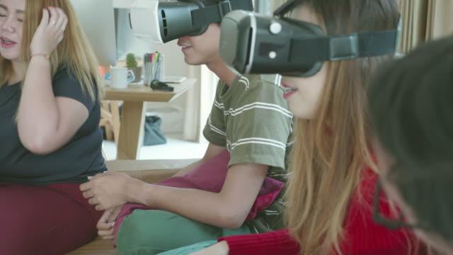 彼らのアパートのリビングルームで一緒にバーチャルリアリティガラスを再生する若いミレニアル世代 - 一緒点の映像素材/bロール