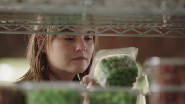 cu. young millennial woman picks up a container of wasabi peas and puts it in her basket - enjoyment stock videos & royalty-free footage