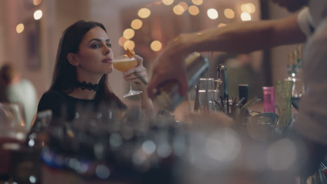 vidéos et rushes de young millennial woman sits alone at a bar using her phone, checks out the bartender - stéréotype de la classe supérieure