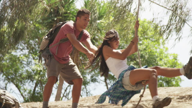 young mixed ethnic man pushing girlfriend on tire swing - partire bildbanksvideor och videomaterial från bakom kulisserna