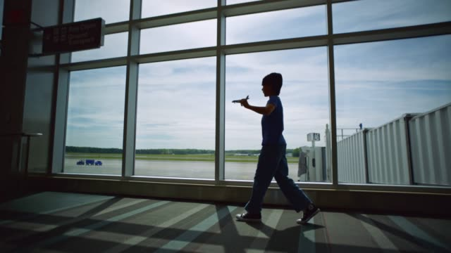 slo mo. young mixed race boy plays with toy airplane near gate window in airport terminal. - pacific islander family stock videos & royalty-free footage