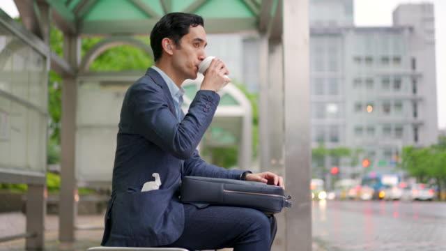 vídeos y material grabado en eventos de stock de joven empresario de carreras mixtas disfrutando de una taza de café mientras se sienta en una estación de autobuses - taza de café