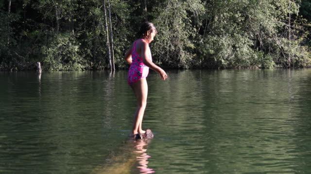 young mixed race girl balances on sunken log, at lake - swimwear stock videos & royalty-free footage