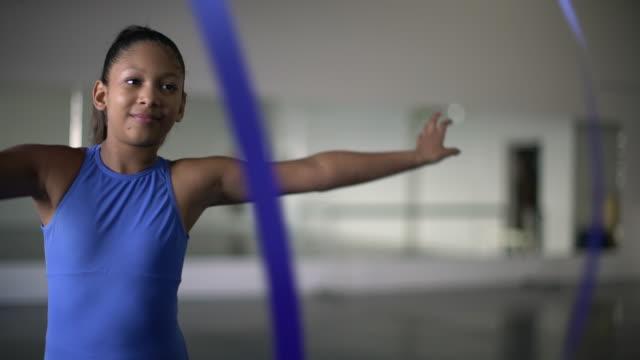 stockvideo's en b-roll-footage met cu young mixed race girl dancing with ribbon in dance studio - dance studio