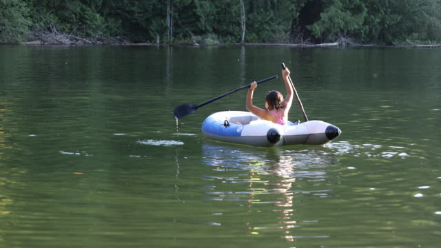 stockvideo's en b-roll-footage met jong gemengd ras meisje peddel rubber dinghy, bij lake - peddel