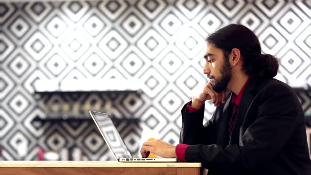 young mixed race indian and caucasian man using computer - guardare verso il basso video stock e b–roll