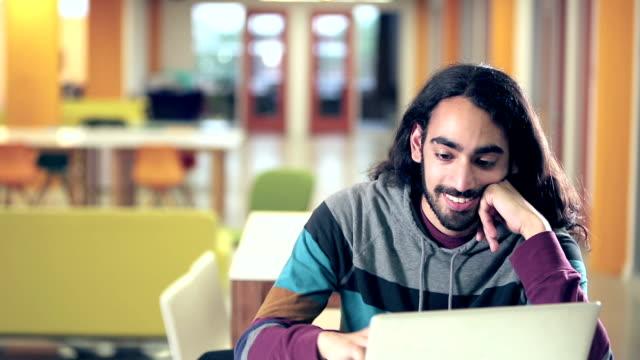 若い混合レース インディアンと白人の人がコンピューターを使用して - indian ethnicity点の映像素材/bロール