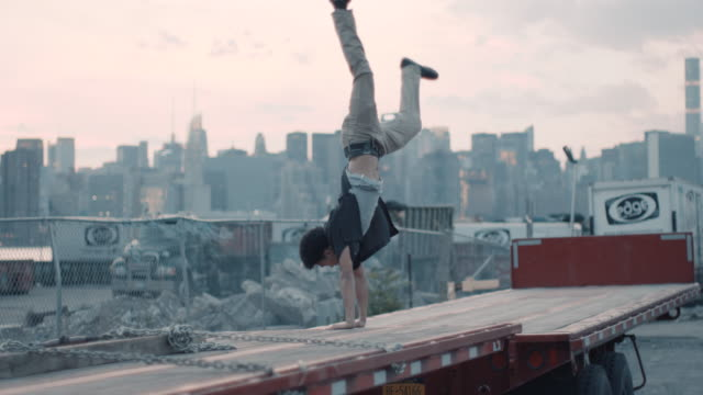 A young mixed race man does a cartwheel with the New York City sunset in the background.
