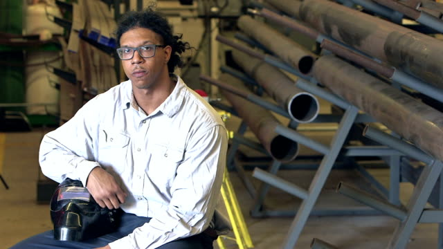 young mixed race man in factory with welding mask - stereotypically working class stock videos and b-roll footage