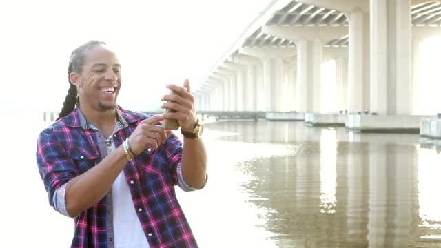 vidéos et rushes de young mélangé homme course sur front de mer à l'aide de téléphone portable - regarder vers le bas