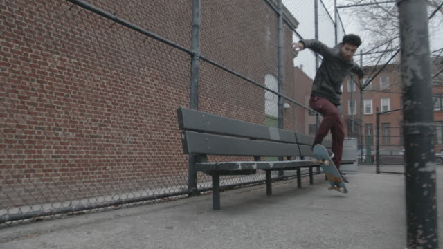 a young mixed race man skateboarding at a park in brooklyn - skateboard stock-videos und b-roll-filmmaterial