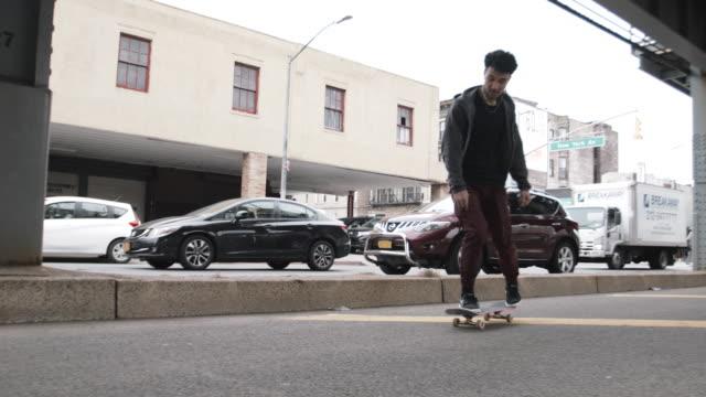a young, mixed race man skateboarding. - full length点の映像素材/bロール