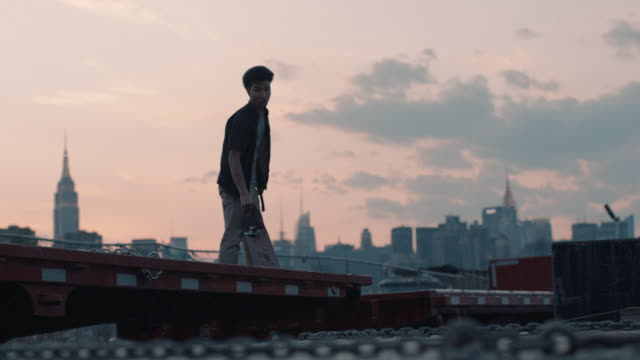 a young, mixed race man skateboards with the nyc skyline in the background. - 柵点の映像素材/bロール