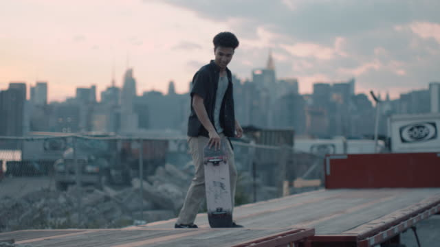 a young, mixed race man skateboards with the nyc skyline in the background. - focus on foreground stock videos & royalty-free footage