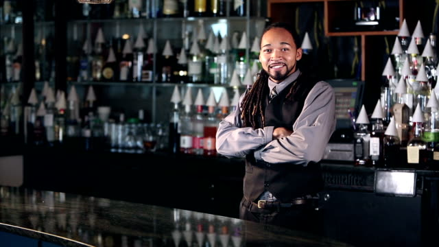 Young mixed race man working as bartender, arms crossed