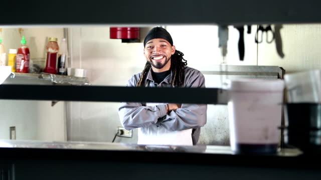 vídeos de stock, filmes e b-roll de homem jovem raça mista que trabalha na cozinha do restaurante - chef de cozinha
