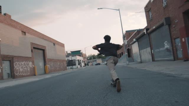 vídeos y material grabado en eventos de stock de a young, mixed race millennial skateboards through the streets of brooklyn, nyc - slow motion - wide angle - sólo hombres jóvenes